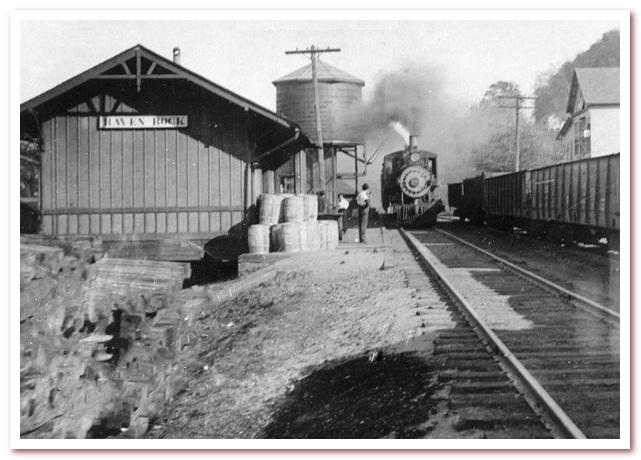 Местный поезд делает остановку у небольшого депо Рэйвен-Рок, Западная Вирджиния у резервуара для воды в начале 1900-х годов.